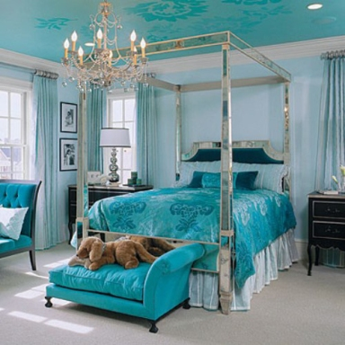 A mirrored canopy bed reflects the teal of the ceiling, bed linens and other furnishings. The black side tables add balance to the room.