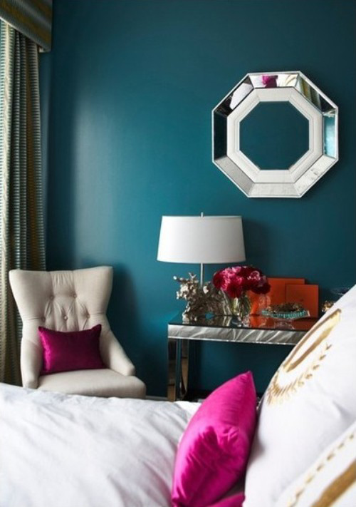 teal accent wall is vibrant against the pristine white of the bed